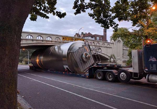 Large Unitank Transported Under Bridge