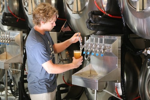 Neil pouring beer from Serving Beer Tanks