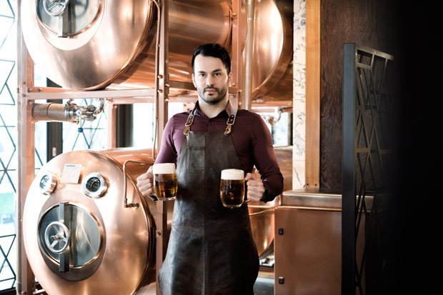 Brewer standing in front of copper serving beer tanks