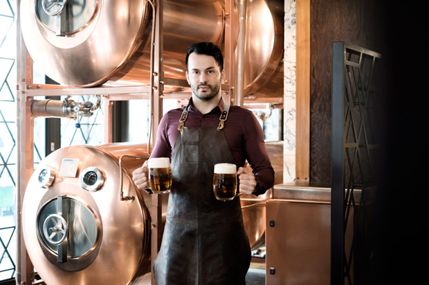 Brasseur debout devant cuves de service en cuivre pour la bière