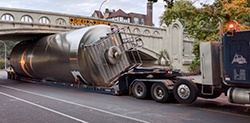 A bright tank being transported on a truck