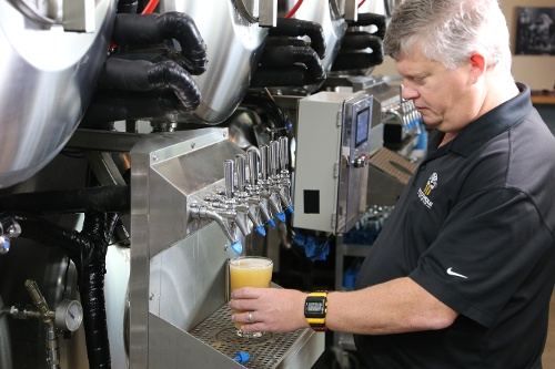 Ole pouring beer from Serving Beer Tanks